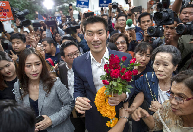 FILE - In this Nov. 20, 2019, file photo, Thanathorn Juangroongruangkit, center, leader of the anti-military Future Forward Party is surrounded by his supporters on his arrival at Constitutional Court in Bangkok, Thailand. Thailand's Constitutional Court on Tuesday, Jan. 21, 2020, acquitted the country's third-biggest political party of seeking the overthrow of the country's constitutional monarchy. (AP Photo/Gemunu Amarasinghe, File)