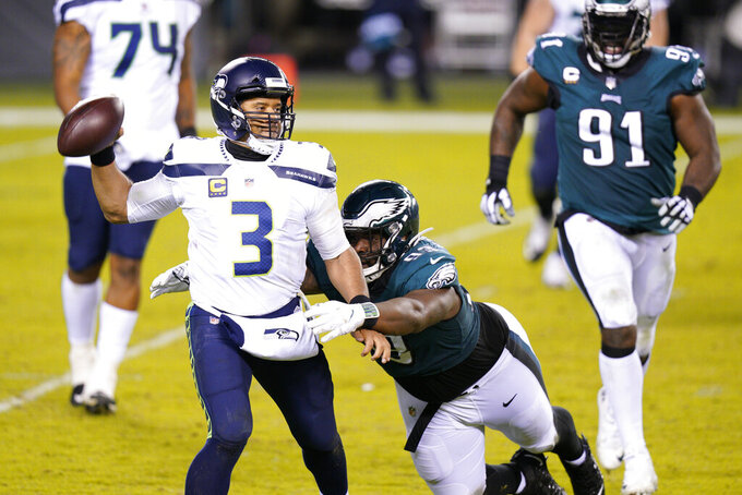 Seattle Seahawks' Russell Wilson (3) tries to get away from Philadelphia Eagles' Javon Hargrave (93) during the second half of an NFL football game, Monday, Nov. 30, 2020, in Philadelphia. (AP Photo/Chris Szagola)