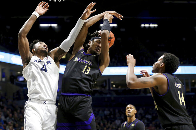 Xavier forward Tyrique Jones (4) and Western Carolina forward Xavier Cork (13) compete for a rebound during the first half of an NCAA college basketball game, Wednesday, Dec. 18, 2019 in Cincinnati. (Kareem Elgazzar/The Cincinnati Enquirer via AP)