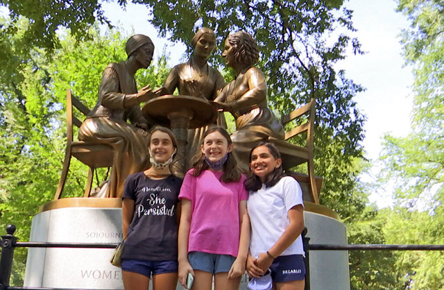 Jaya Shri, 13, , right stands with friends at the unveiling of a new statue honoring suffragettes in Central Park on Wednesday, Aug. 26, 2020.  bronze statue depicting women's rights pioneers Sojourner Truth, Elizabeth Cady Stanton and Susan B. Anthony was unveiled in Central Park on Wednesday. It's the 167-year-old park's first monument honoring real historical women — as opposed to fictional heroines like Alice in Wonderland and Shakespeare's Juliet.  (AP Photo/Ted Shaffrey)