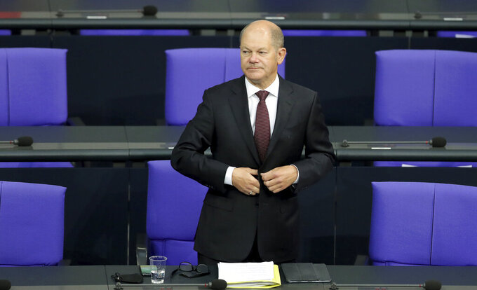 File - In this Tuesday, Sept. 29, 2020 file photo German Finance Minister Olaf Scholz arrives for a budget debate as part of a meeting of the German federal parliament, Bundestag, at the Reichstag building in Berlin, Germany. German lawmakers presenting a report into the collapse of payment processing company Wirecard accused the country's finance minister and auditors Ernst and Young of numerous oversight failings. (AP Photo/Michael Sohn, file)