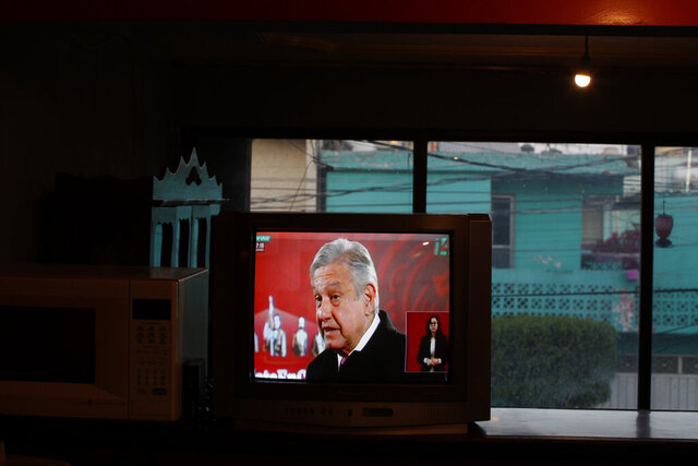 Mexico's President Andres Manuel Lopez Obrador is seen on a TV screen as Rafael Silva watches the live broadcast of the president's daily, morning press conference known as