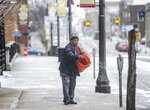 Emilio Rosas spreads salt on the sidewalk of several businesses in Lansing, Michigan's Old Town Sunday, April 15, 2018. (Robert Killips/Lansing State Journal via AP)