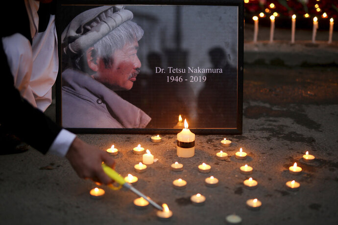 An Afghan man lights a candle in front of a portrait of Tetsu Nakamura,  a Japanese physician engaged in aid work who was killed Wednesday, Dec. 4 in a shooting in eastern Afghanistan, during a vigil in Kabul, Afghanistan on Thursday, Dec. 5, 2019.   (AP Photo/Altaf Qadri)