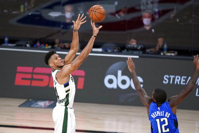 Giannis Antetokounmpo de los Bucks de Milwaukee lanza el balón superando a Gary Clarke del Magic de Orlando en el quinto juego de la serie de primera ronda de la Conferencia Este el sábado 29 de agosto del 2020 en Lake Buena Vista, Florida. (AP Photo/Ashley Landis)