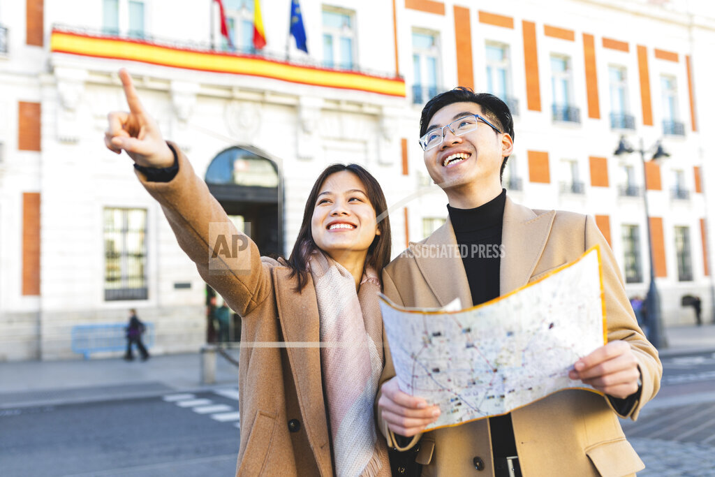 Spain, Madrid, happy young couple with map exploring the city