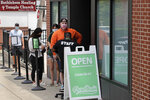 In this Wednesday, June 24, 2020, photograph, customers wait in line at Pure Oasis, a Black-owned recreational marijuana dispensary, in the Grove Hall neighborhood of Boston. Many from outside Boston have recently shopped and supported the store which was robbed and vandalized earlier in the month. (AP Photo/Charles Krupa)