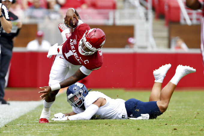Arkansas quarterback KJ Jefferson (1) is tripped up by Rice defender Cameron Montgomery (1) as he runs the ball during the first half of an NCAA college football game, Saturday, Sept. 4, 2021, in Fayetteville, Ark. (AP Photo/Michael Woods)
