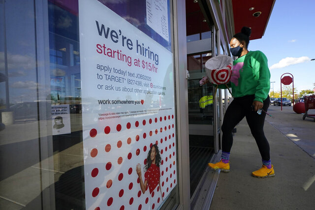 FILE - In this Sept. 30, 2020, file photo, a passerby walks past a hiring sign while entering a Target store in Westwood, Mass. The U.S. unemployment rate dropped to 7.9% in September, but hiring is slowing and many Americans have given up looking for work, the government said Friday, Oct. 2, in the final jobs report before the voters decide whether to give President Donald Trump another term. (AP Photo/Steven Senne, File)