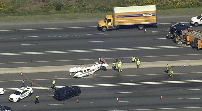 This image provided by WJLA-TV shows emergency personnel responding to a small plane that crashed into a vehicle on Route 50 near Freeway Airport in Bowie, Md., on Thursday, Sept. 12, 2019. Police say it's believed the pilot was trying to land at the airport.  (WJLA-TV via AP)  DC OUT