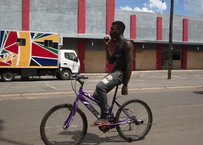 A young man on a bicycle passes a mobile clinic, background left, run by the Reproductive Health and HIV Institute (RHI) in the Soshanguve Township, north of Pretoria, South Africa, Thursday, Nov. 26 2020. The successful trials of a new injectable drug that needs to be taken every eight weeks to prevent HIV infection is being lauded on World AIDS Day as a turning point for the fight against a global health threat that's been eclipsed by the coronavirus pandemic. (AP Photo/Denis Farrell)