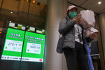 A woman wearing a face mask stands in front of an electronic board showing Hong Kong share index outside a local bank in Hong Kong, Friday, Feb. 14, 2020. Asian shares mostly fell Friday as investors turned cautious following a surge in cases of a new virus in China that threatens to crimp economic growth and hurt businesses worldwide. (AP Photo/Vincent Yu)