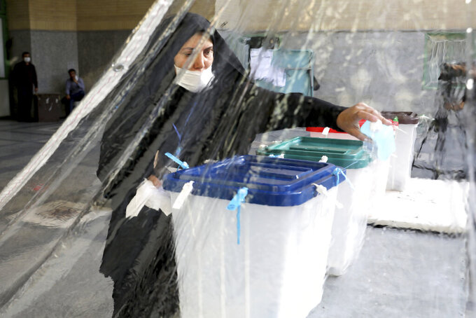 An Iranian election official prepares ballot boxes at a polling station in Tehran, Iran, Friday, June 18, 2021. Iran began voting Friday in a presidential election tipped in the favor of a hard-line protege of Supreme Leader Ayatollah Ali Khamenei, fueling public apathy and sparking calls for a boycott in the Islamic Republic. (AP Photo/Ebrahim Noroozi)