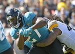 FILE - In this Nov. 18, 2018, file photo, Jacksonville Jaguars running back Leonard Fournette, left, runs for yardage as he is stopped by Pittsburgh Steelers outside linebacker Bud Dupree, right, during the first half of an NFL football game in Jacksonville, Fla. A person familiar with the situation says the Jacksonville Jaguars have notified running back Leonard Fournette that his suspension late last month voided the remaining guarantees in his four-year rookie contract. The person spoke to The Associated Press on the condition of anonymity Sunday night, Dec. 30, 2018 .(AP Photo/Phelan M. Ebenhack, File)