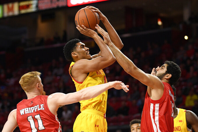 Maryland forward Ricky Lindo Jr., center, shoots between Fairfield guard Calvin Whipple (11) and forward Wassef Methnani, right, during the first half of an NCAA college basketball game, Tuesday, Nov. 19, 2019, in College Park, Md. (AP Photo/Nick Wass)