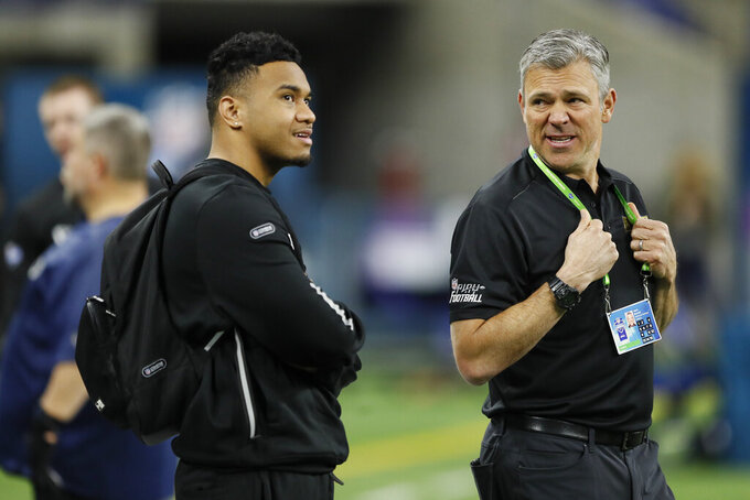 FILE - In this Feb. 27, 2020, file photo, Alabama quarterback Tua Tagovailoa, left, talks with NFL Legend Mark Brunell, right, at the NFL football scouting combine in Indianapolis. Mark Brunell knows his 19-year NFL career is one to make today's NFL quarterback prospects envious. What he wanted them to avoid was starting out like he did. The former Jacksonville Jaguars star just wrapped up his fifth season serving as a mentor at the NFL scouting combine, where he and fellow alum Chad Pennington guided the soon-to-be rookies through the week as they're poked and prodded, tested and interrogated. (AP Photo/Charlie Neibergall, File)
