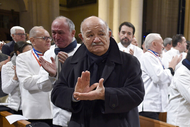 FILE - In this Friday, Jan. 26, 2018 file photo, French chef Pierre Troisgros applauds as the coffin of late French chef Paul Bocuse leaves the Saint-Jean Cathedral, in Lyon, central France. French media say Pierre Troisgros, one of France's top chefs who helped reinvent the country's traditional cuisine, has died. He was 92. The French press quoted the head of the Maison Troisgros, Patrice Laurent, saying the chef died Wednesday, Sept. 23, 2020 at his home in Coteau, near Roanne in the Loire region where his restaurant is located. (Philippe Desmazes/Pool Photo via AP, file)