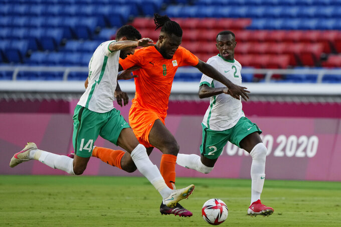 Ivory Coast's Franck Kessie is challenged by Saudi Arabia's Ali Alhassan during a men's soccer match at the 2020 Summer Olympics, Thursday, July 22, 2021, in Yokohama, Japan. (AP Photo/Kiichiro Sato)