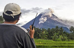 A volunteer uses his walkie talkie as he monitors Mount Merapi during an eruption in Sleman, Wednesday, Jan. 27, 2021. Indonesia's most active volcano erupted Wednesday with a river of lava and searing gas clouds flowing 1,500 meters (4,900 feet) down its slopes. (AP Photo/Slamet Riyadi)