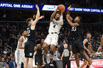 Georgetown guard Jagan Mosely (4) goes to the basket between Butler forward Sean McDermott (22) and guard Henry Baddley (20) during the second half of an NCAA college basketball game, Tuesday, Jan. 28, 2020, in Washington. Butler won 69-64. (AP Photo/Nick Wass)