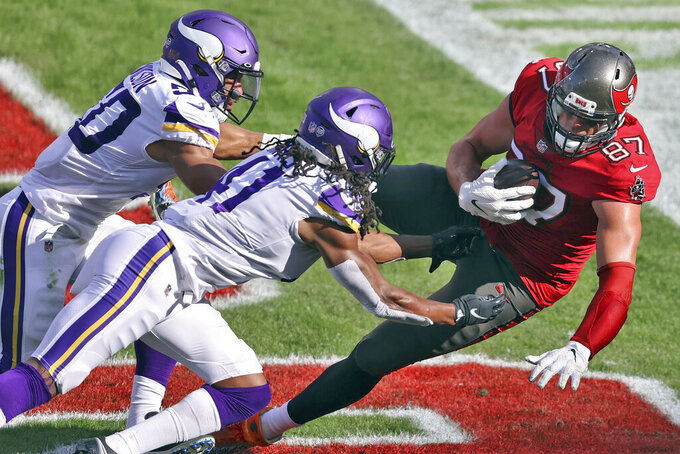 Tampa Bay Buccaneers tight end Rob Gronkowski (87) pulls in a 2-yard touchdown pass from Tom Brady after getting past Minnesota Vikings outside linebacker Eric Wilson (50) and free safety Anthony Harris (41) during the second half of an NFL football game Sunday, Dec. 13, 2020, in Tampa, Fla. (AP Photo/Mark LoMoglio)