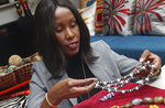 In this Monday, Dec. 3, 2018, photo, Shamila Nduriri, who owns Dalasini, an upscale jewelry company, holds some of her jewelry in her Minneapolis apartment. Nduriri, who studied finance in college, saved aggressively when she worked for a corporation and continues to put money aside now that she owns Dalasini. (AP Photo/Jim Mone)
