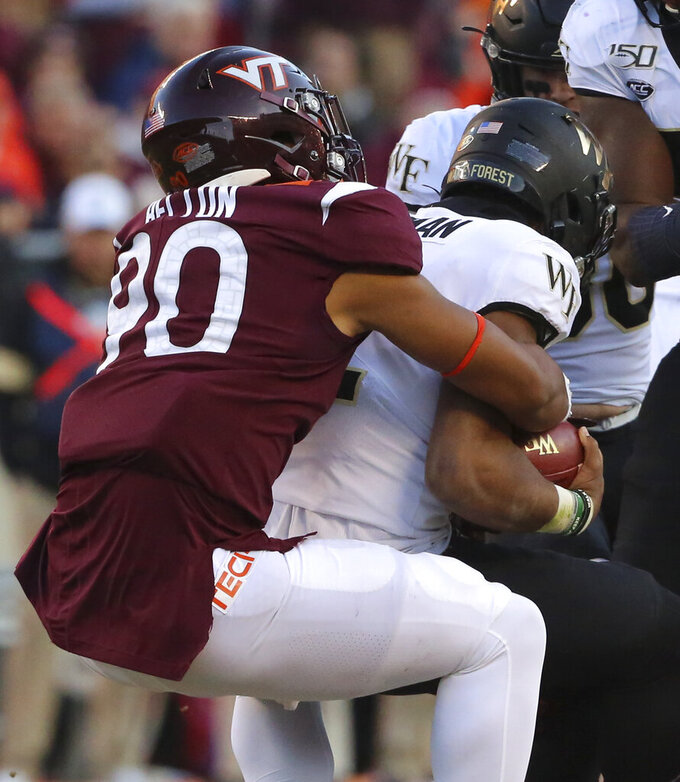 Virginia Tech's Jaevon Becton (90) sacks Wake Forest quarterback Jamie Newman (12) in the first half of an NCAA college football game Saturday, Nov. 9, 2019, in Blacksburg, Va. (Matt Gentry/The Roanoke Times via AP)