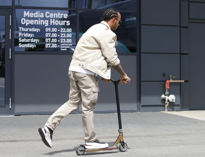 Mercedes driver Lewis Hamilton of Britain rides a scooter in the paddock of the Silverstone racetrack, in Silverstone, England, Thursday, July 11, 2019. The British Formula One Grand Prix will be held on Sunday. (AP Photo/Luca Bruno)