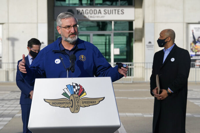 Indiana Gov. Eric Holcomb speaks after receiving his Johnson & Johnson COVID-19  vaccine during the state's first mass vaccination clinic at the Indianapolis Motor Speedway, Friday, March 5, 2021, in Indianapolis. The state health department said nearly 17,000 people had filled up four days of appointments for the speedway clinic being held Friday through Monday. (AP Photo/Darron Cummings)