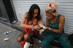 Honduran sex workers Carolina and Angora, split a small meal, as they wait for clients outside the Revolution subway station in Mexico City, Sunday, March 14, 2021. Angora, 27, who said she began sex work at age 12, used to earn enough money to send back home. Now she is homeless, living with multiple STDs, and struggles with alcohol abuse. (AP Photo/Rebecca Blackwell)