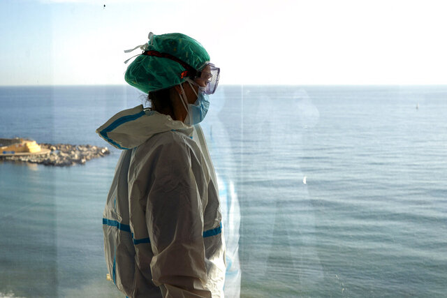 Nurse Marta Fernandez looks at the sea from a windows during a brief break at the COVID-19 ward at the hospital del Mar in Barcelona, Spain, Wednesday, Nov. 18, 2020. (AP Photo/Emilio Morenatti)