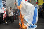 Demonstrators set fire to a makeshift Israeli flag during an anti-U.S. annual rally in front of the former U.S. Embassy in Tehran, Iran, Monday, Nov. 4, 2019. Reviving decades-old cries of