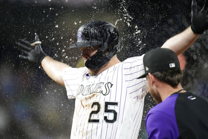 Teammates shower Colorado Rockies' C.J. Cron after he drove in the winning run against the Milwaukee Brewers in the 10th inning of a baseball game Friday, June 18, 2021, in Denver. The Rockies won 6-5. (AP Photo/David Zalubowski)