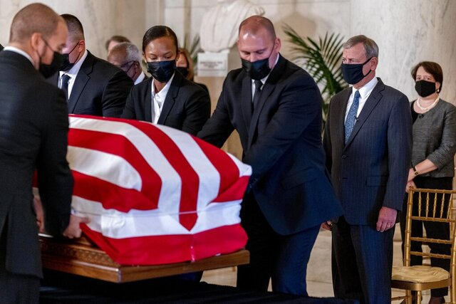 Chief Justice of the United States John Roberts, second from right, and Justice Elena Kagan, right, watch as the flag-draped casket of Justice Ruth Bader Ginsburg arrives at the Supreme Court in Washington, Wednesday, Sept. 23, 2020. Ginsburg, 87, died of cancer on Sept. 18. At far right is Associate Justice Elena Kagan. (AP Photo/Andrew Harnik, Pool)