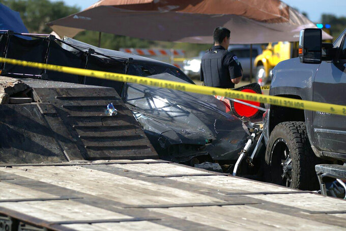 In this photo provided by Louis Amestoy, a police officer stands watch over the scene of a fatal drag racing crash at the Kerrville-Kerr County Airport in Kerrville, Texas, on Oct. 23, 2021. (Louis Amestoy via AP)