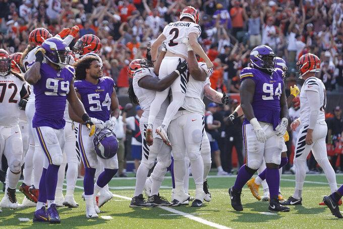 The Minnesota Vikings walk off the field as the Cincinnati Bengals hoist their kicker Cincinnati Bengals kicker Evan McPherson (2) after he made a field goal to win during overtime of an NFL football game, Sunday, Sept. 12, 2021, in Cincinnati. The Bengals won 27-24. (AP Photo/Jeff Dean)