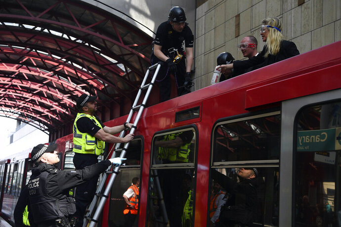 Police begin to remove climate activists who glued themselves on top of a Dockland Light Railway train at Canary Wharf station in east London as part of the ongoing climate change protests in the capital on Wednesday April 17, 2019. The group Extinction Rebellion is calling for a week of civil disobedience against what it says is the failure to tackle the causes of climate change. (Kirsty O'Connor/PA via AP)