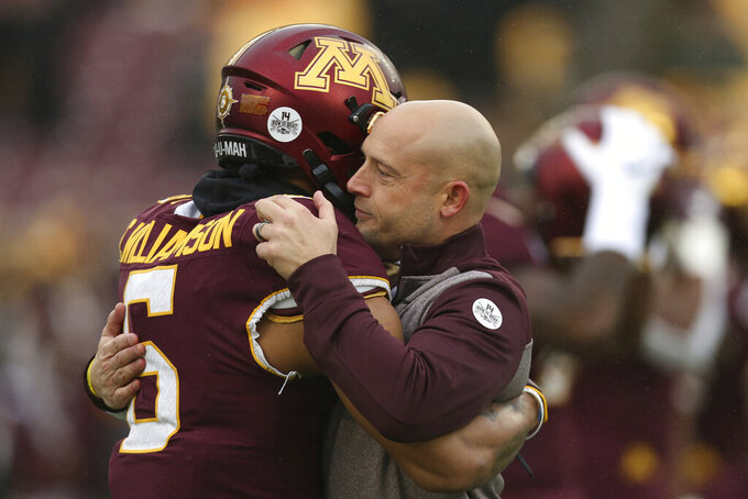 Minnesota head coach P.J. Fleck hugs defensive back Chris Williamson (6) during an NCAA college football game against Wisconsin, Saturday, Nov. 30, 2019, in Minneapolis. Wisconsin won 38-17. (AP Photo/Stacy Bengs)