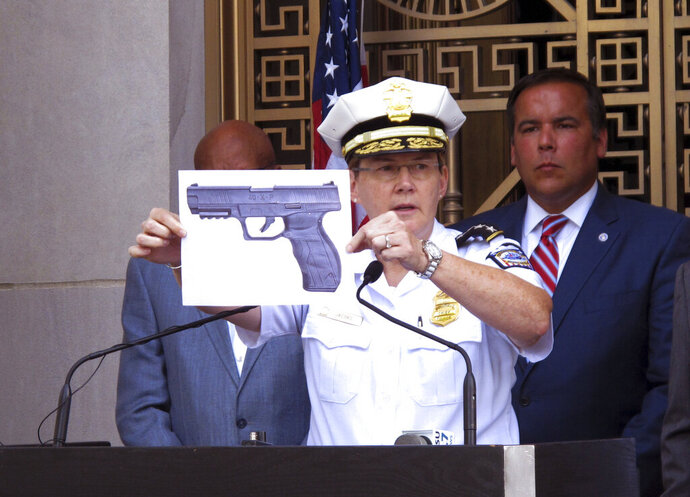 FILE - In this Sept. 15, 2016 file photo, Columbus Police Chief Kim Jacobs holds up a photo showing the type of BB gun that police say a 13-year-old Tyre King pulled from his waistband just before he was shot and killed by police investigating an armed robbery report in Columbus, Ohio.  Four teenagers who were with King before he was fatally shot by a white police officer have been added as third-party defendants in a civil rights lawsuit over his death, even though his family doesn't believe the teens should be held financially responsible. The teens were added to the federal case over the death of King at the request of the city of Columbus, meaning they could be on the hook if the city or the officer is found liable for damages in the lawsuit.   (AP Photo/Andrew Welsh-Huggins, File)