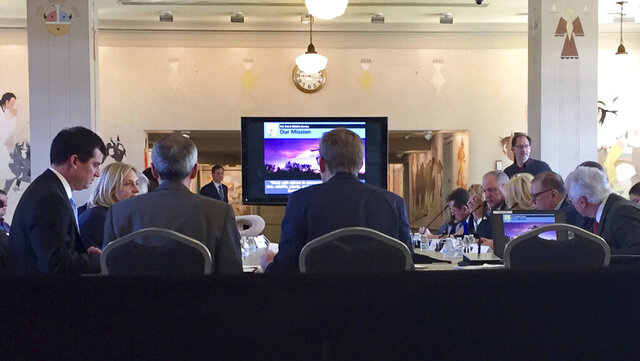 FILE - In this March 16, 2018, file photo, a new U.S. advisory board is shown meeting for the first time to help rewrite federal rules for importing the heads and hides of African elephants, lions and rhinos at the Interior Department in Washington. The Trump administration has disbanded its advisory board created to help boost trophy hunting and relax federal rules for importing the heads and hides of African elephants, lions and rhinos. (AP Photo/Michael Biesecker, File)
