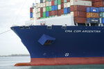 In this April 6, 2021 photo, crew members stand on the bow as the CMA CGM Argentina arrives at PortMiami, the largest container ship to call at a Florida port in Miami.  Importers are contending with a perfect storm of supply trouble — rising prices, overwhelmed ports, a shortage of ships, trains, trucks — that is expected to last into 2022.  (AP Photo/Lynne Sladky)