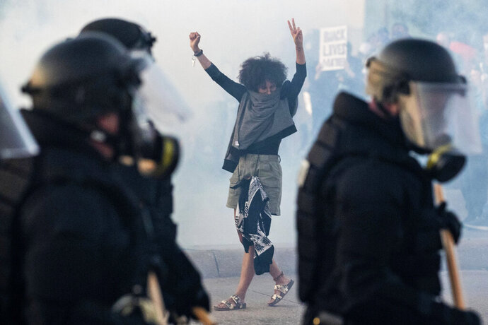A woman flashes the peace sign while walking backwards in a cloud of tear gas during a protest at 72nd and Dodge Streets on Friday, May 29, 2020. Protests have been erupting all over the country after George Floyd died earlier this week in police custody in Minneapolis. (Chris Machian/Omaha World-Herald via AP)