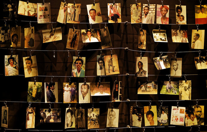 FILE - In this Friday, April 5, 2019 file photo, family photographs of some of those who died hang on display in an exhibition at the Kigali Genocide Memorial centre in the capital Kigali, Rwanda. Felicien Kabuga, one of the most wanted fugitives in Rwanda's 1994 genocide who had a $5 million bounty on his head, has been arrested in Paris, authorities said Saturday, May 16, 2020. (AP Photo/Ben Curtis, File)