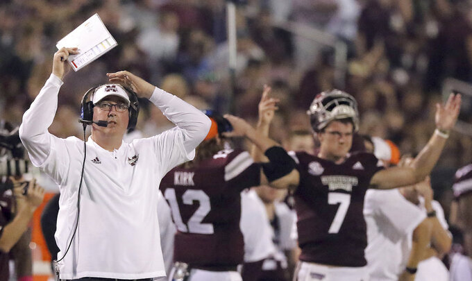 Mississippi State head coach Joe Moorhead, left and quarterback Nick Fitzgerald (7) both react to the replay on the video board while game officials reviewed the play making sure Fitzgerald had indeed crossed the goal line and scored a touchdown during the first half of their NCAA college football game against Auburn on Saturday, Oct. 6, 2018, in Starkville, Miss. (AP Photo/Jim Lyle)