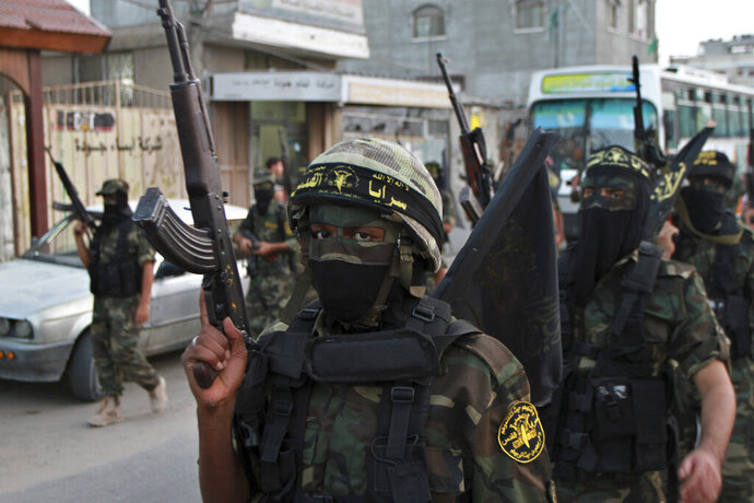 FILE - In this Oct. 2, 2012 file photo, masked militants of the Islamic Jihad group march during a rally marking the 17th anniversary of the death of the group's leader Fathi Shekaki, in Rafah Refugee camp in the southern Gaza Strip. The group was founded in 1981 with the aim of establishing an Islamic Palestinian state in the West Bank, Gaza and all of what is now Israel. It is designated a terrorist organization by the U.S. State Department, European Union and other governments. (AP Photo/Adel Hana, File)