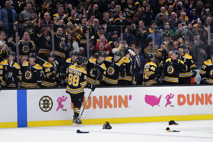 Boston Bruins right wing David Pastrnak (88) is congratulated by teammates after his third goal of the game during the second period of an NHL hockey game against the Montreal Canadiens in Boston, Wednesday, Feb. 12, 2020. (AP Photo/Charles Krupa)