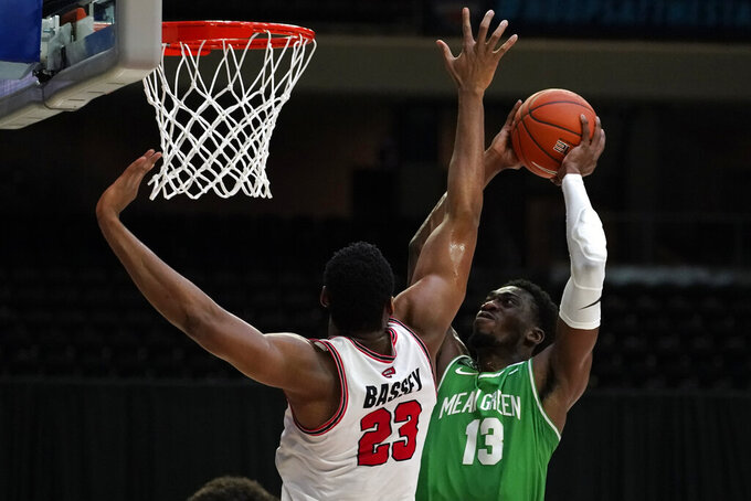 Western Kentucky center Charles Bassey (23) tries to block a shot by North Texas forward Thomas Bell (13) during the first half of the championship game in the NCAA Conference USA men's basketball tournament Saturday, March 13, 2021, in Frisco, Texas. (AP Photo/Tony Gutierrez)