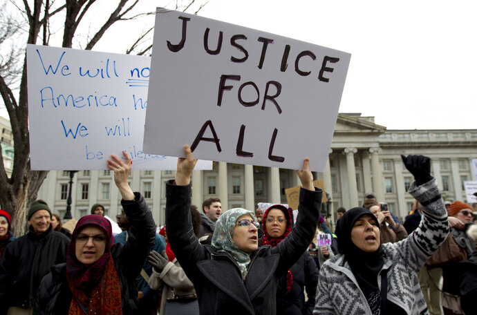 FILE - In this Jan. 29, 2017 file photo, demonstrators carrying signs chant as they protest outside of the White House in Washington during a demonstration to denounce President Donald Trump's executive order banning travel to the U.S. by citizens of Iraq, Syria, Iran, Sudan, Libya, Somalia and Yemen. Trump's travel ban on travelers from predominantly Muslim countries is headed back to a federal appeals court, three years after it was first imposed. On Tuesday, Jan. 27, 2020, the 4th U.S. Circuit Court of Appeals in Richmond is scheduled to hear arguments in three lawsuits filed by U.S. citizens and permanent residents whose relatives have been unable to enter the U.S. because of the ban. (AP Photo/Jose Luis Magana, File)
