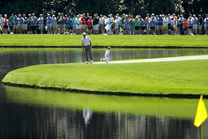 "FILE - In this April 10, 2019, file photo, Dustin Johnson and son Tatum stand on the ninth green during the par-3 golf tournament at the Masters in Augusta, Ga. The Par 3 Contest is out at the spectator-free Masters in November. ESPN's ""College GameDay"" is in. Augusta National announced Tuesday, Oct. 27, 2020, more changes to a Masters tournament that will be unlike any of the previous 83. The most unusual of all is ESPN's popular college football pregame show taking place on a stage that overlooks Ike's Pond and the ninth green of the Par 3 course. (AP Photo/Matt Slocum, File)"
