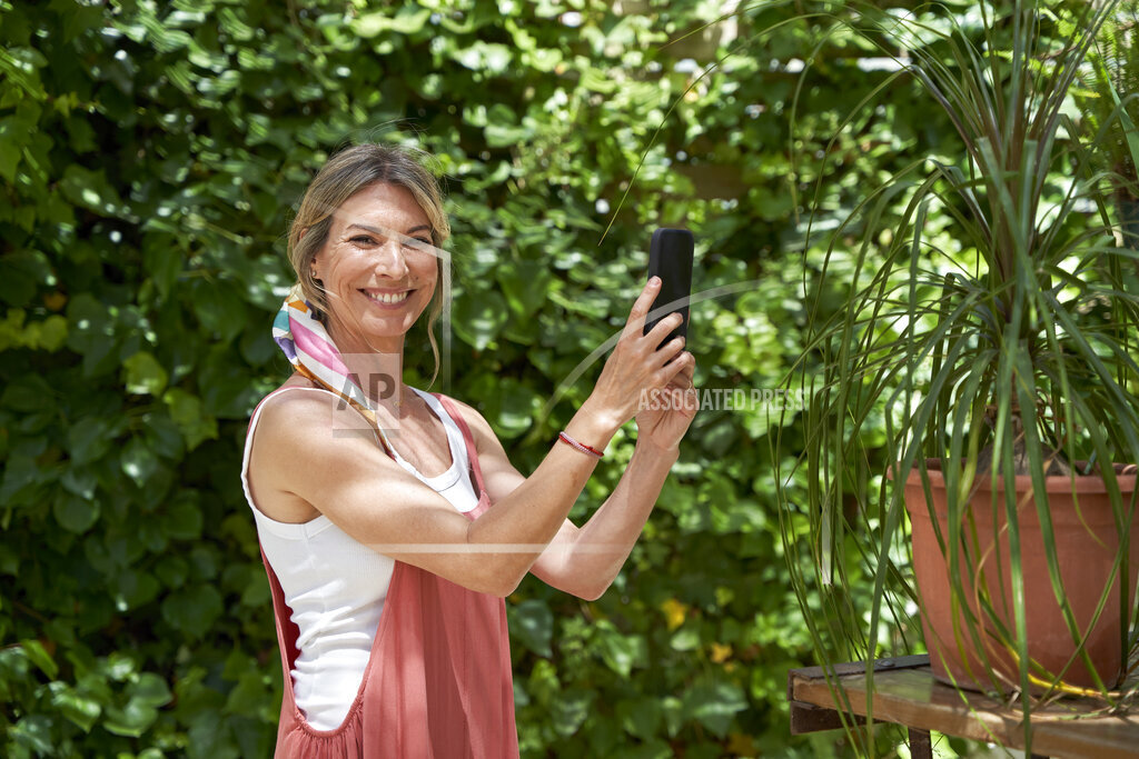 Smiling woman photographing plants through smart phone while standing at backyard